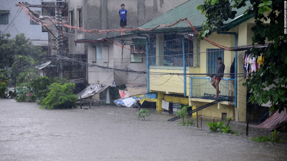 Men watch flooding from their homes in Manila on August 20.