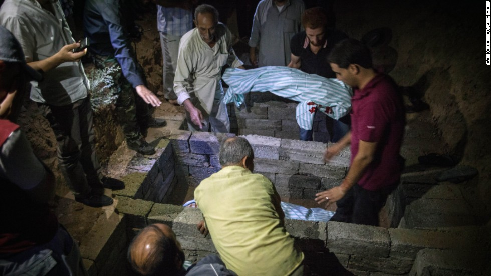 Men bury the bodies of six members of the same family killed in a bombing in Raqqa on Saturday, August 10.