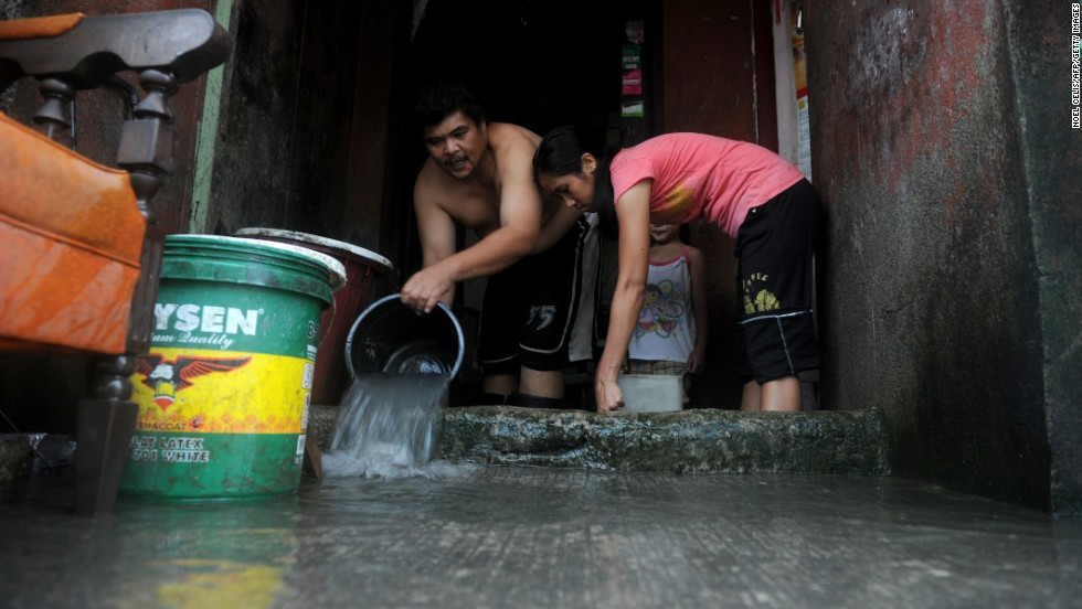 People bail water from their house in Noveleta on August 21.