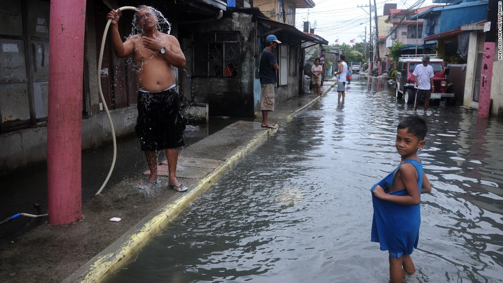 A man washes his face beside a flooded street in Kawit on August 21.