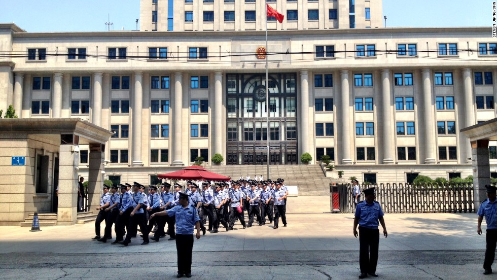 Police march outside the courthouse in Jinan on August 21.