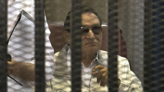 Mubarak and his sons Gamal, left, and Alaa are seen behind the defendants' cage during their retrial at the Police Academy in Cairo. Mubarak was granted a retrial.