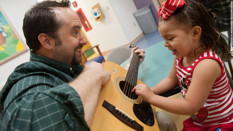 Brian Jantz, a music therapist at Boston Children's Hospital, plays with a patient, Yaneishka Trujillo. Jantz uses music to engage with children.