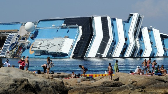 People enjoy a day in the sun with a view of the cruise liner on July 1, 2012.