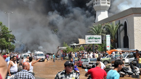 Smoke is seen above people gathering outside a mosque on the site of a powerful explosion in the northern Lebanese city of Tripoli on Friday, August 23. Two bombings killed dozens of people. The first blast occurred near a mosque led by a Sunni sheikh known for his links to Syrian rebels, Lebanon