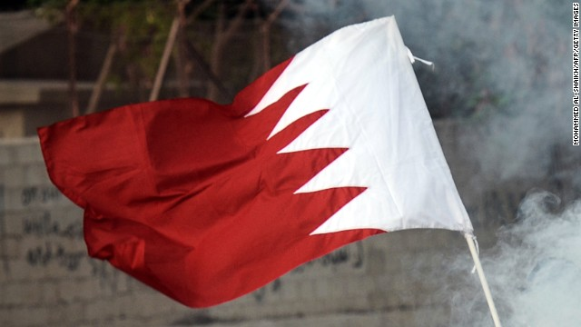 A protester holds the Bahrain flag and runs for cover from tear gas in the village of Shakhora, west of Manama, on August 14, 2013.