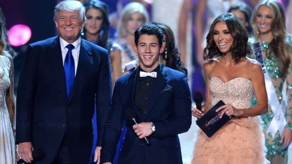 Trump appears on stage with singer Nick Jonas and television personality Giuliana Rancic during the 2013 Miss USA pageant.
