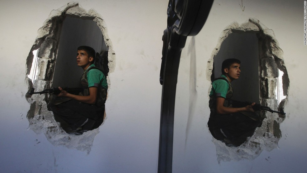 A young Free Syrian Army fighter is reflected in a mirror as he takes position in a house in Aleppo on Thursday, August 22.