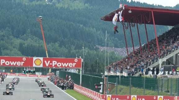 """Drivers perform a warm-up lap at the Spa-Francorchamps circuit as Greenpeace militants deploy a banner reading """"ARCTIC OIL? SHELL NO!"""""""