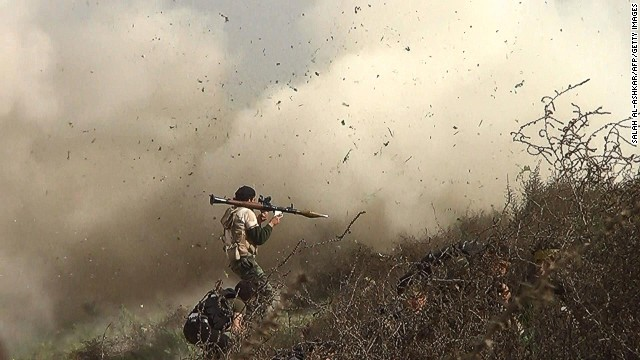 An image grab taken from a video shows opposition fighter holding a rocket propelled grenade (RPG) as his fellow comrades take cover from an attack by regime forces on August 26, 2013 during clashes over the strategic area of Khanasser, situated on the only road linking Aleppo to central Syria.