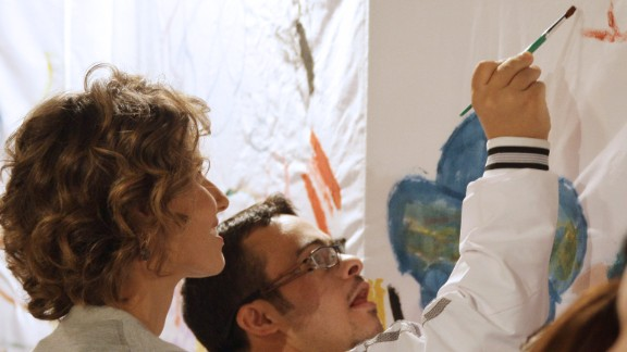 During an athletics gathering in Damascus, al-Assad watches as a young person paints on September 5, 2010.