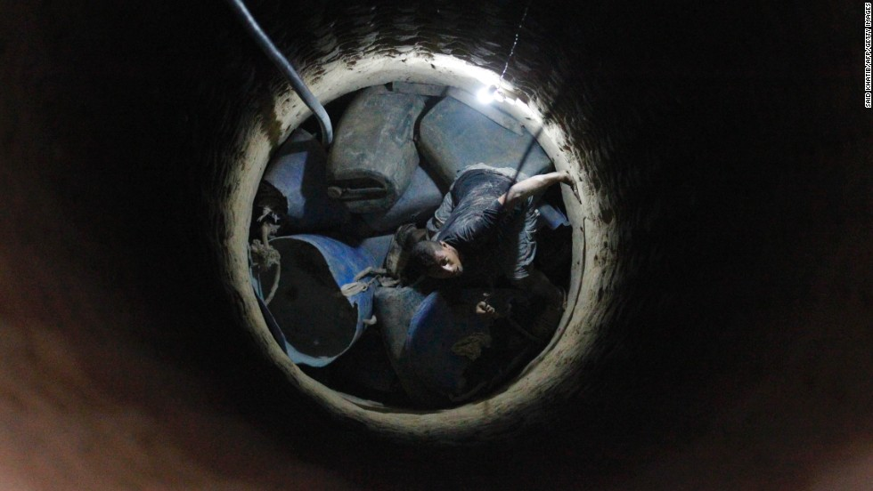 "AUGUST 28 - GAZA, PALESTINIAN TERRITORIES: A Palestinian tunnel worker peers inside a smuggling tunnel dug beneath the Gaza-Egypt border in southern Gaza on August 27. <a href=""http://cnn.com/2013/02/26/world/meast/egypt-gaza-tunnels"">An Egyptian court ordered the destruction of the tunnels in February.</a>"