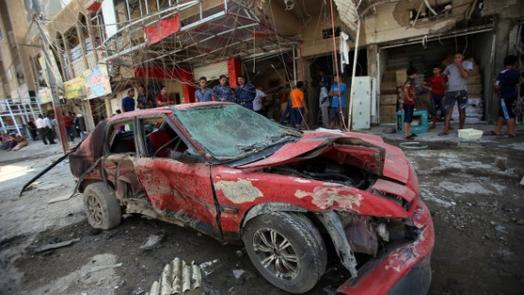 Iraqi civilians check the site of an explosion in Baghdad on Wednesday.