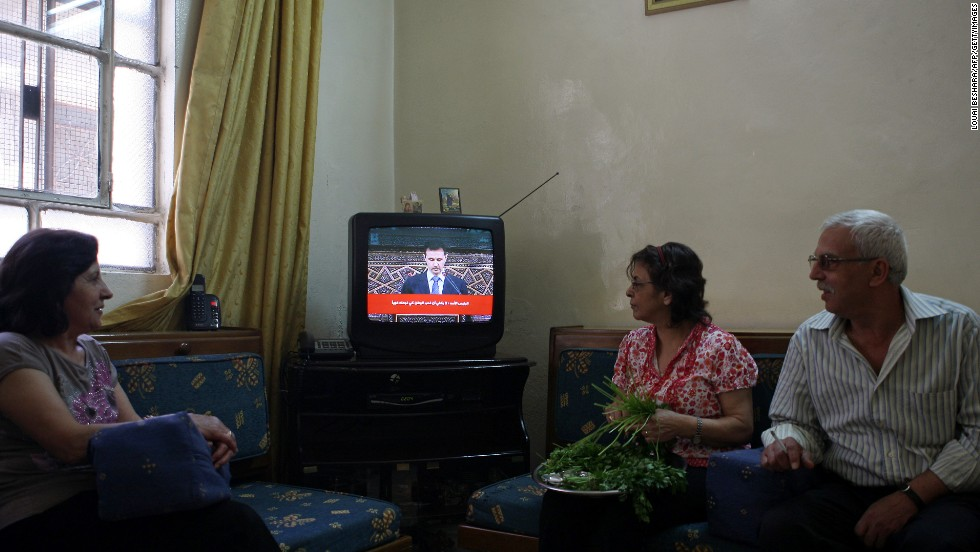 "Syrians listen to a televised speech by al-Assad in Damascus on June 3, 2012. Al-Assad said that his government faces a foreign plot to destroy Syria and blamed ""monsters"" for the Houla massacre in a rare televised speech delivered in parliament."