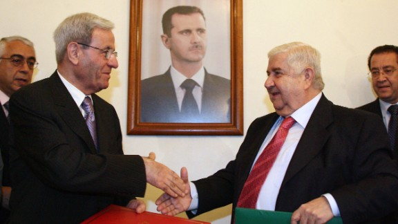 Syrian Foreign Minister Walid Muallem, right, and his Lebanese counterpart, Fawzi Salloukh, shake hands under a portrait of al-Assad in Damascus on October 15, 2008, after signing an agreement to restore diplomatic relations.