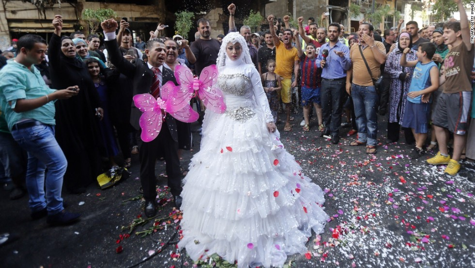 A crowd cheers as a Lebanese bride and groom pose for pictures at the site of a car bomb just days before in Beirut, Lebanon.