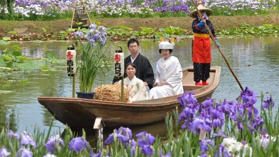 A Japanese bride and her groom sail through a canal for their wedding procession after their wedding ceremony at Katori city in Chiba prefecture.