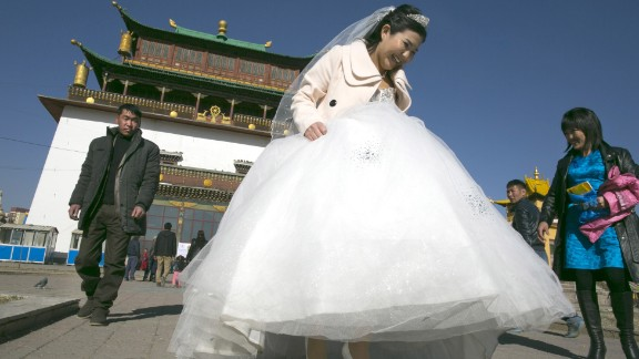 A bride walks holding her wedding dress at the Gandan monastery on October 18, 2012, a special day on the lunar calendar for wedding ceremonies, in Ulaanbaatar, Mongolia.