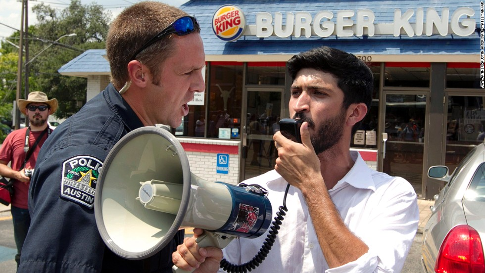 A police officer orders Greg Casar of the Workers Defense Project to get off the property of a Burger King in Austin, Texas, on  August 29, 2013. Casar was leading a group of about 200 people supporting the nationwide fast food strike. Fast food workers in 60 cities across the country walked off the job in a protest for higher wages.