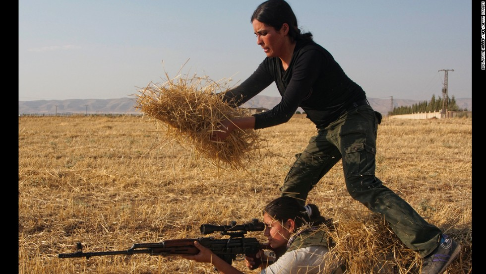 A Syrian Kurd uses hay to hide another woman in a training session organized by the Kurdish Women's Defense Units on Wednesday, August 28, in a northern Syrian border village. They're preparing if the area comes under attack.