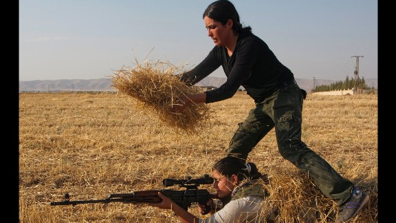A Syrian Kurd uses hay to hide another woman in a training session organized by the Kurdish Women