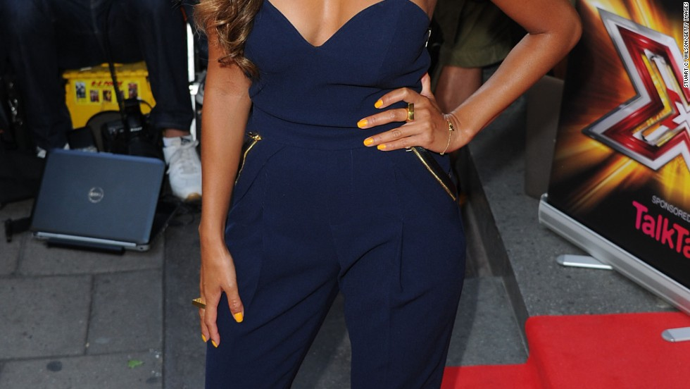 "Nicole Scherzinger shields herself from the camera flashes at the London press launch for ""X Factor"" on August 29."