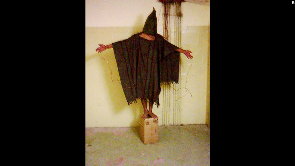 A hooded detainee in U.S. custody during the Iraq War stands on a box with electrical wires hooked up to his fingers. The image became a symbol of the Abu Ghraib prison abuse scandal after it was released, among others, in late April 2004. It did what a written report could not do, showing front-and-center what human rights groups had been saying for months: that prisoners were being abused at the hands of U.S. troops. The fallout was immediate, both overseas and at home.