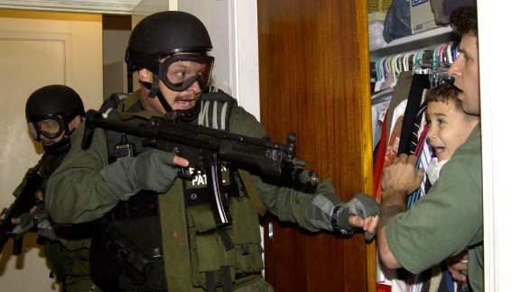 """During a raid at a Miami home in 2000, armed federal agents confront Elian Gonzalez, 6, and one of the men who helped rescue the boy. Gonzalez watched his mother drown when the boat smuggling them from Cuba capsized. Under international law, U.S. authorities were required to return the boy to his father in Cuba. Alan Diaz's photograph of the saga's defining moment won a Pulitzer Prize. """"The cry I heard that day I had never heard in my life,"""" Diaz said a decade later. """"A cry like that will haunt anyone forever."""""""