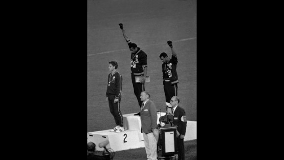 American athletes Tommie Smith, center, and John Carlos raise their fists and hang their heads while the U.S. national anthem plays during their medal ceremony at the 1968 Summer Olympics in Mexico City. Their black power salute became front page news around the world as a symbol of the struggle for civil rights. To their left stood Australian Peter Norman, who expressed his support by wearing an Olympic Project for Human Rights badge.
