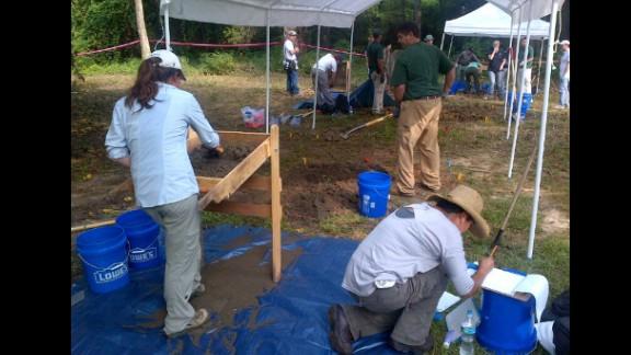 The team excavates and examines the bodies.