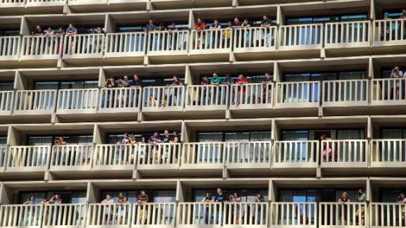 People watch the parade from balconies at the Hyatt Regency.