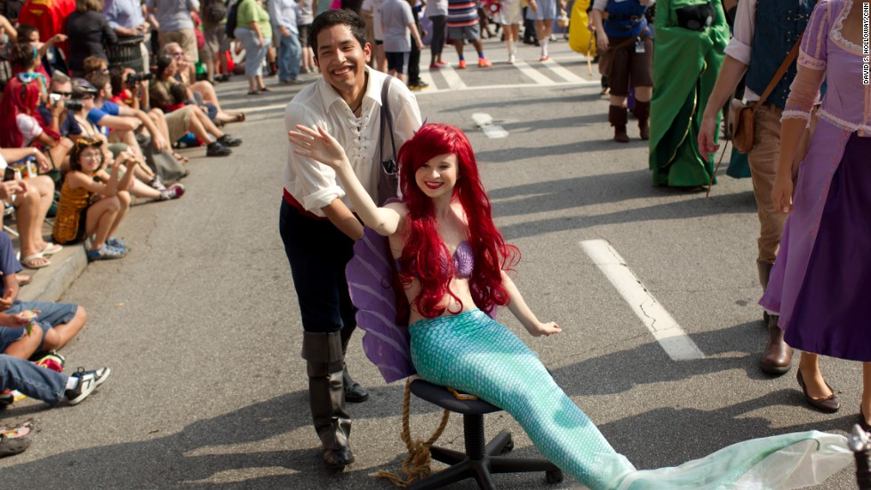 "Ariel, ""The Little Mermaid,"" gets a little dry-land help moving along the parade route."