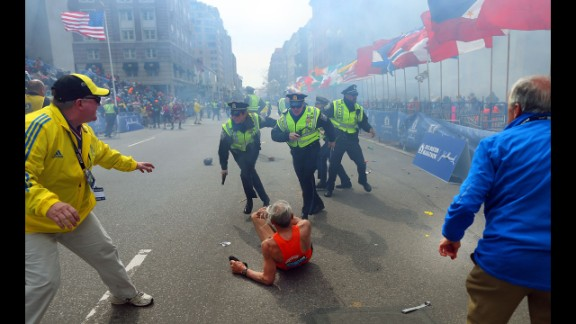 """Boston Globe photographer John Tlumacki was near the finish line when 78-year-old runner Bill Iffrig was knocked down by the first explosion at the Boston Marathon on April 15. The bombings left three people dead and injured more than 100. Iffrig got up and finished the race. Tlumacki's image of the fallen runner was widely published and selected for the cover of """"Sports Illustrated."""""""
