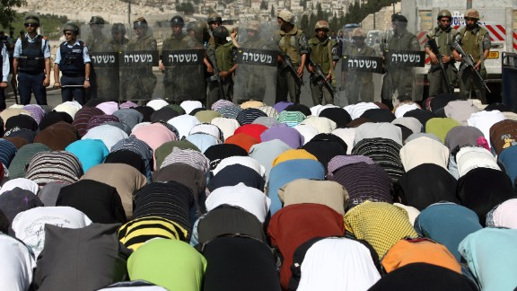 Israeli police stand guard as Palestinian Muslims perform Friday prayers outside Jerusalem