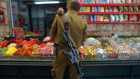 In among the holy sites, daily life roars on: Souks crowd the narrow, stone-flagged alleyways; children go to school; libraries jostle with restaurants. Here, a soldier buys candy at the Mahane Yehuda Market.