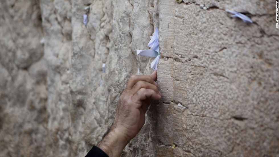 A man sticks a note into the Western Wall. This is part of the original Jewish temple complex in the Old City.