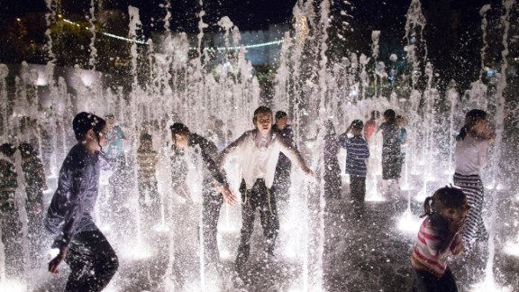 Children play in a fountain at a park in Jerusalem.