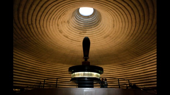 People look at the Isaiah Scroll, one of the Dead Sea Scrolls, in the vault of the Shrine of the Book at the Israel Museum. With more than 200 museums, Israel has the highest number of museums per capita in the world. Here is a list of 10 of the best.