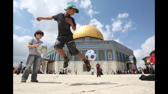 Daily life in Jerusalem: A boy plays with a soccer ball in front of the Dome of the Rock. It