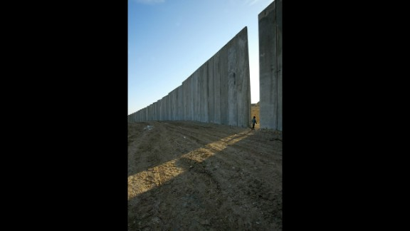 A child walks through a gap in the concrete blocks of a security wall in the West Bank village of Eizariya, east of Jerusalem, in 2003. Take a walking tour of East Jerusalem or a pilgrimage to the Palestinian city of Bethlehem, and you