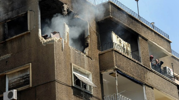 Syrian firefighters try to extinguish a fire after a missile hit a residential building in Damascus, Syria, on September 2.