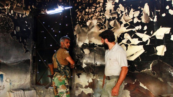 Free Syrian Army fighters talk inside a burnt house in Aleppo on September 3.