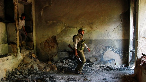 Free Syrian Army fighters walk inside a damaged house in Aleppo on September 3.