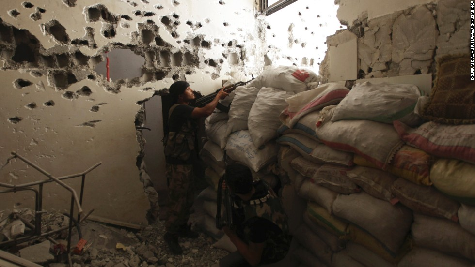 Free Syrian Army fighters take their positions behind piled sandbags, as one of them points his weapon, in Deir ez-Zor on September 2.