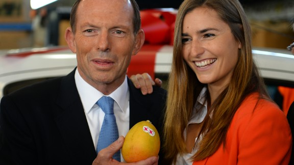 """Australian opposition leader Tony Abbott poses with a mango and one of his """"not bad looking daughters."""" What will he say next?"""
