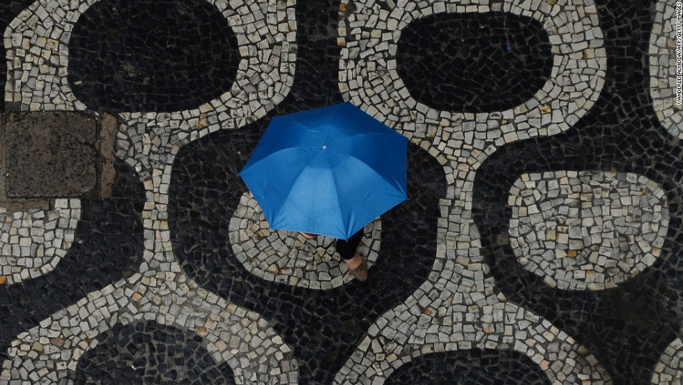 A pedestrian walks in the rain on a street in Rio de Janeiro on September 4.
