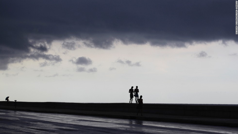 Storm clouds cover the sky as people walk on Havana's El Malecon seafront boulevard on September 4.