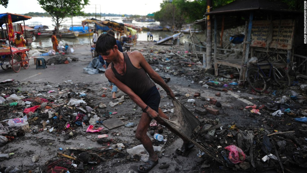 An Indian man clears debris from the banks of the Ganga River as floodwaters recede in Allahabad on September 3.