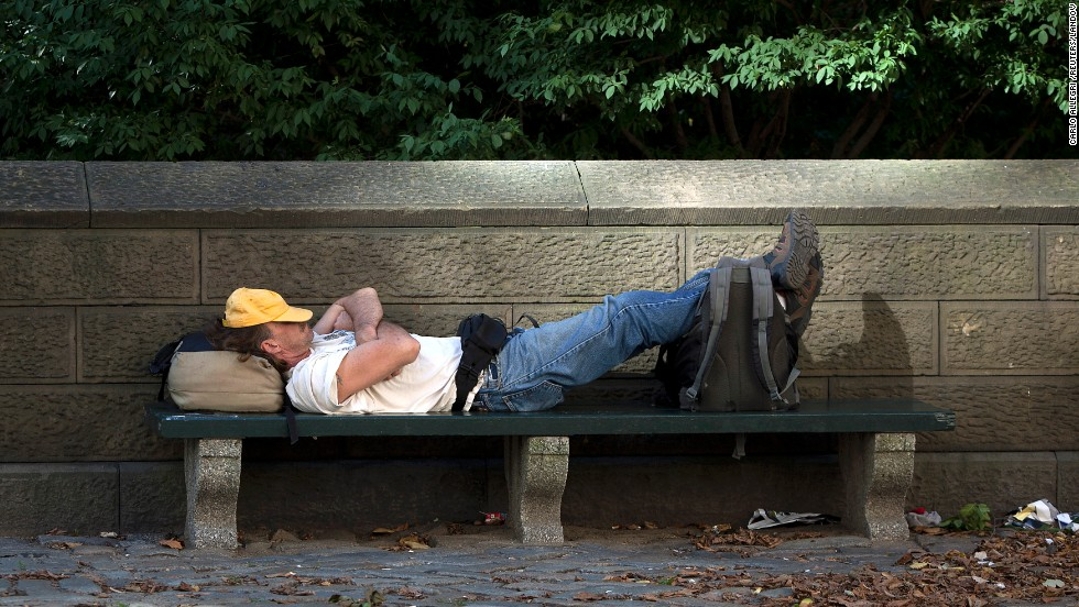 A man takes a nap on a park bench in the late afternoon sun along 5th Avenue at Central Park in New York on September 3.