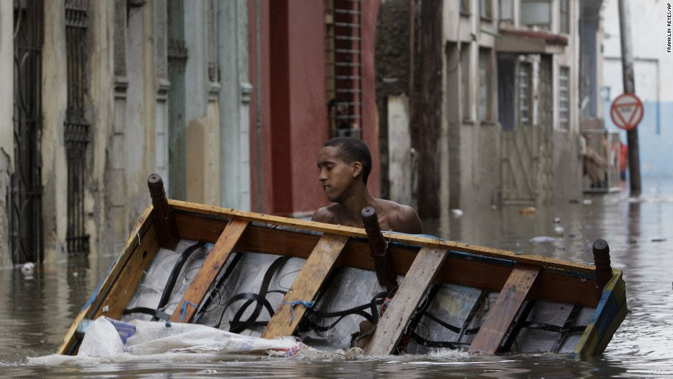 A man carries a ruined bed away from his home while walking through floodwaters in Old Havana, Cuba, on September 3.
